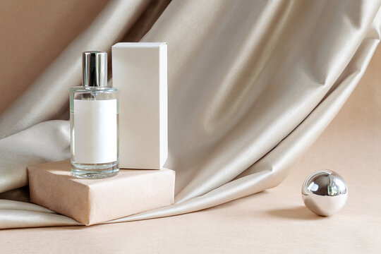 Glass bottle of aromatic luxury niche floral perfume with box on podium on background of fabric drapery. Cosmetics products for personal care concept. Minimalist packing, branding.