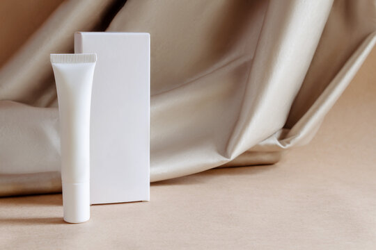 White tube of moisturizing luxury niche face cream gel with box on background of fabric drapery. Cosmetics products for personal care, hygiene concept. Minimalist packing, branding.