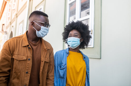 Happy young couple outdoors, spending time together, walk down the street with masks on their faces, life during a virus pandemic