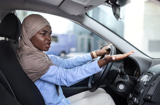 Stressed black muslim woman arguing with someone while driving car