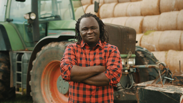 Young african farmer with crossed hands over the chest in front of tractor and haystack. High quality photo