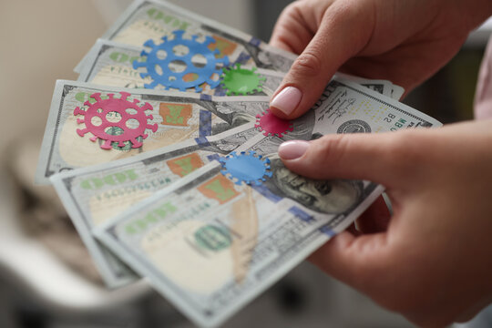 Female hand holds one hundred dollar bills on pasted bacteria virus. What diseases can you get infected through money concept