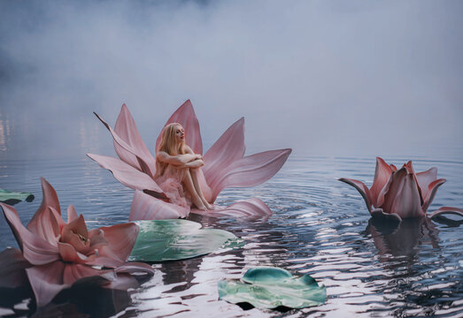 Happy young little blonde woman sits in a huge pink lotus flower that floats on the water. Fantasy artistic photo Beautiful girl in a fairy tale Thumbelina. Goddess of nature on the river in blue fog