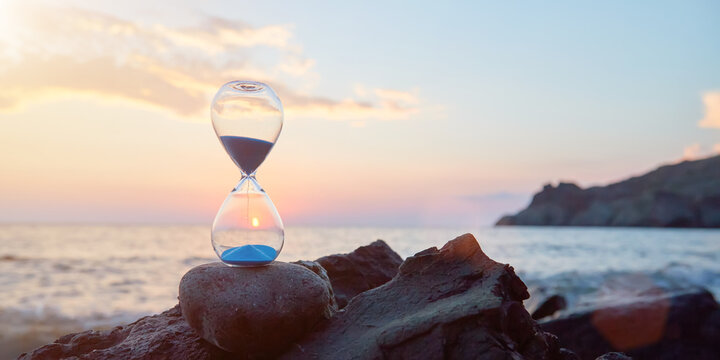 Hourglass with blue falling sand inside. Ocean landscape and golden hour. Time fly and need in rest concept, copy space