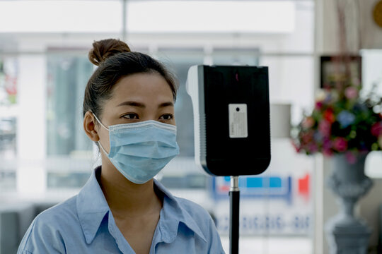 The Asian tourist woman has checked body temperature with a thermal Temperature scanner detector, new normal and travel safety concept