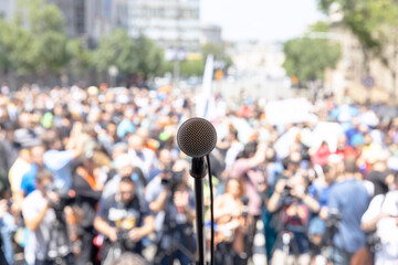 Focus on microphone, blurred group of people at mass protest in the background