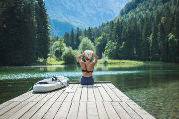 Young Caucasian woman sitting on the dock, preparing for stand up paddle boarding workout