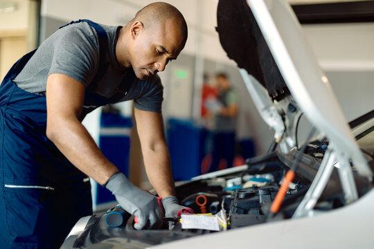 African American mechanic repairing car engine in a workshop.