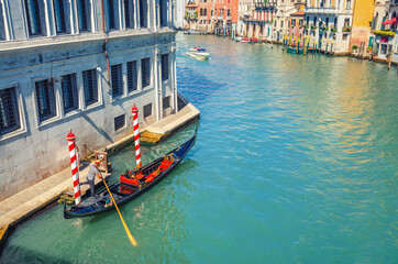 Gondolier on sailing gondola traditional boat in water of Grand Canal waterway in Venice historical city centre with Venetian architecture colorful buildings around. Veneto Region, Northern Italy.