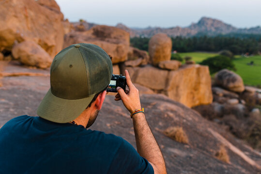 Rear view of resolute backpacker with baseball cap  taking picures with digital camera at dusk with rice fields and palm trees at background  in Hampi Island, India, Karnataka.