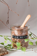 Fototapeta flax seeds in glass jar with wooden spoon and natural elements leaves and bark on grey background