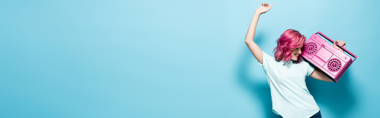 young woman with pink hair holding vintage tape recorder and dancing on blue background, panoramic shot