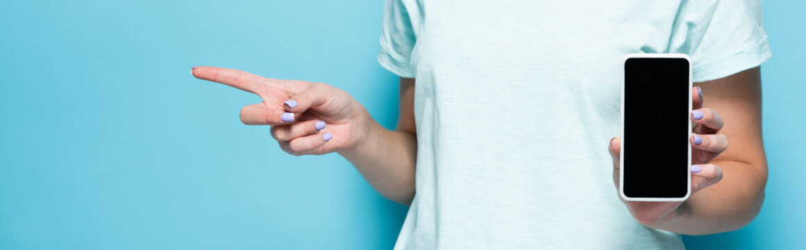 cropped view of young woman holding smartphone with blank screen and pointing aside on blue background, panoramic shot