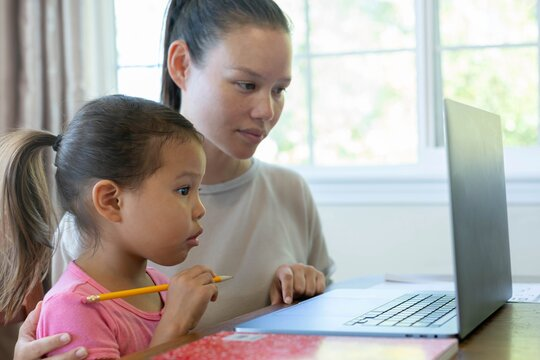 Child distance learning on computer with parent. Online school at home.