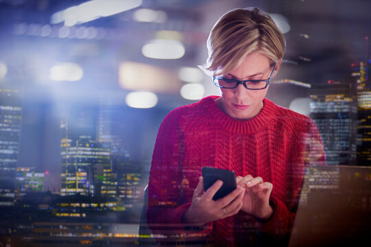 Businesswoman using smart phone with cityscape in background