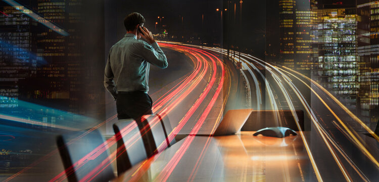 Businessman talking on smart phone in city at night