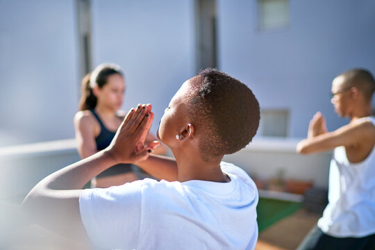 Serene young woman practicing yoga on sunny balcony