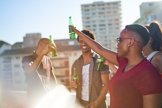 Carefree young friends drinking beer on sunny urban balcony