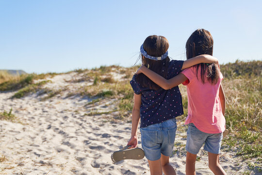Affectionate sisters walking on sunny beach path