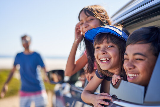 Portrait happy kids leaning out sunny car window