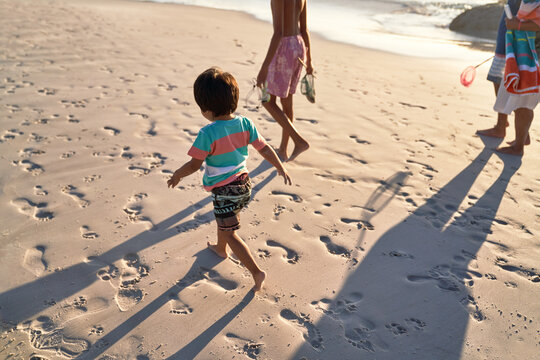 Cute boy running on beach with family