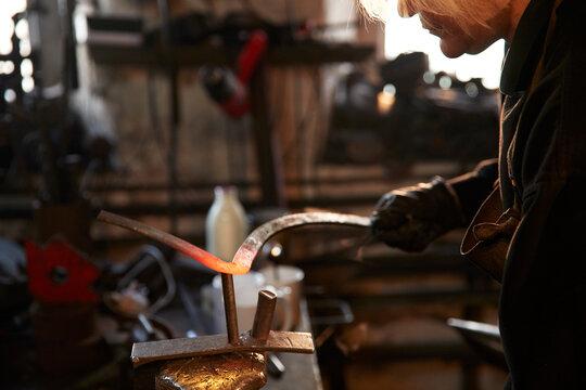 Female blacksmith shaping steel in workshop