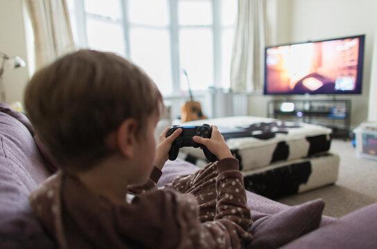 Boy playing video game on living room sofa