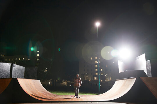Young man skateboarding on ramp at skate park at night