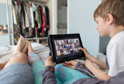 POV family with digital tablet video chatting with friends on bed