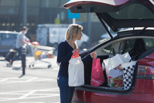 Woman loading groceries into back of car in sunny parking lot