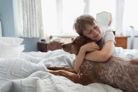 Cute boy hugging dog on bed