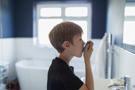 Boy with asthma using inhaler in bathroom