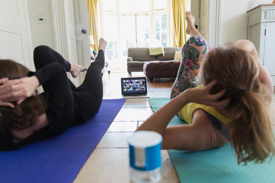 Mother and daughter taking online yoga class at home