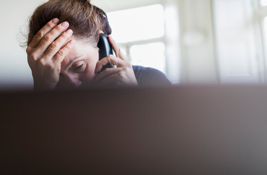 Tired woman talking on telephone at laptop