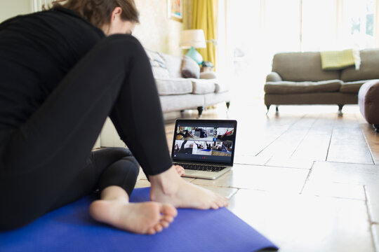 Woman taking online yoga class at laptop