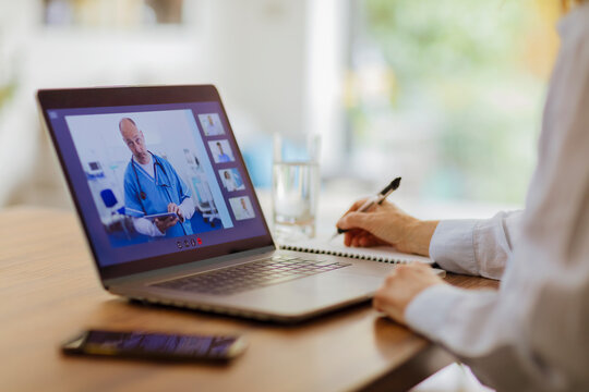 Woman video conferencing with doctor at laptop