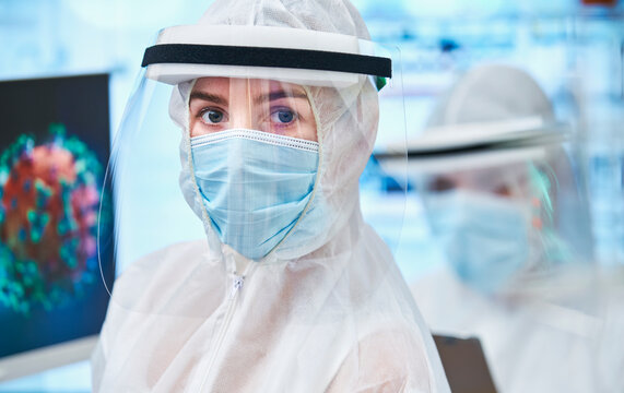 Portrait confident female scientist in clean suit studying coronavirus