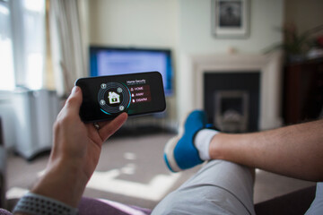 POV Man checking home security on smart phone in living room