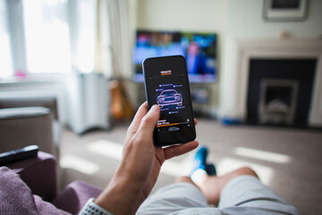 POV Man checking remote car control on smart phone in living room