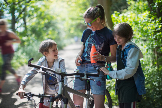Mother and sons drinking water on bike ride in sunny park