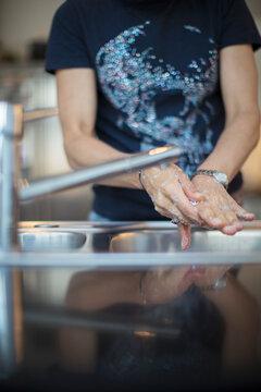 Woman washing hands at kitchen sink