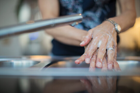 Close up woman washing hands with soap at kitchen sink