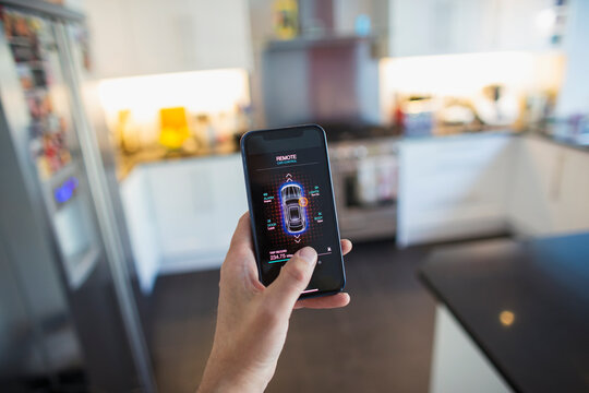 POV Man securing car alarm from smart phone screen in kitchen