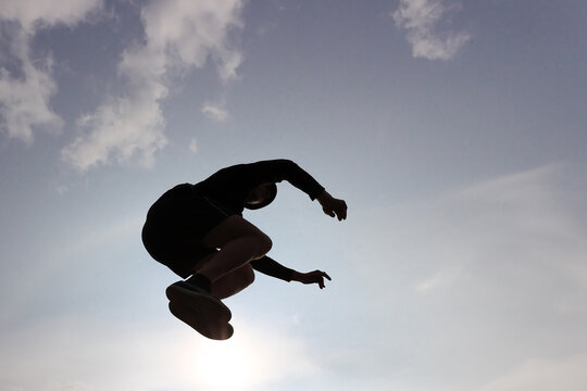 The guy is engaged in parkour jumping against the sky