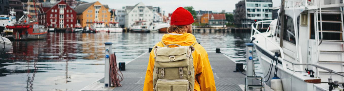 Man tourist with touristic rucksack wearing yellow jacket walking among authentic fishing boats. Wide image