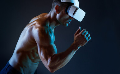 Muscular model sports young man in glasses of virtual reality on dark background. Fashion portrait of strong brutal guy. Sexy torso. Male flexing his muscles. VR. Blue neon light.