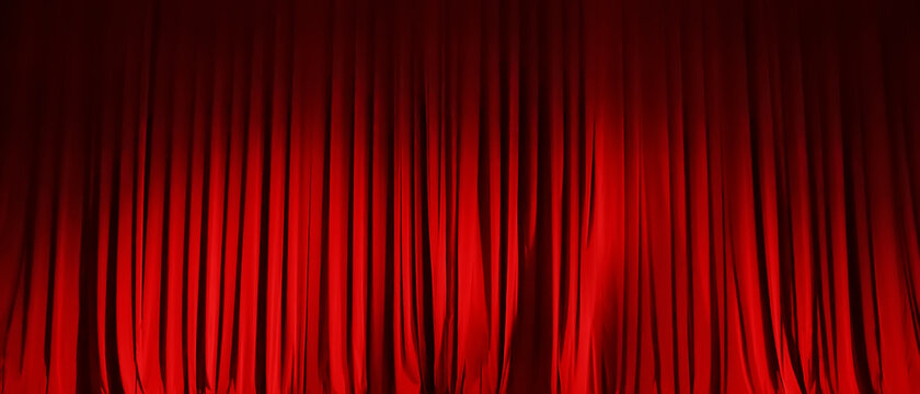 Closed red curtain of stage in spotlight before show.