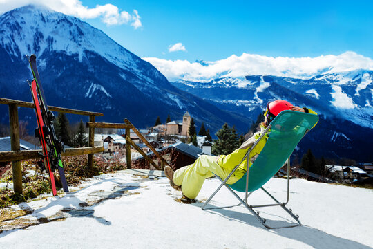 Young woman rest in the deck chair near pair of ski observing mountains and Alpine peaks