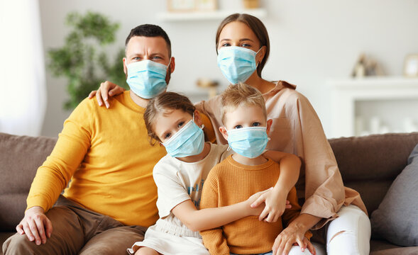 family in protective medical masks in the midst of the coronavirus pandemic at home.