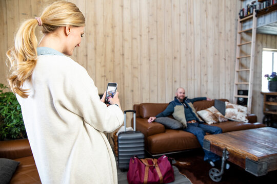 Woman photographing vacation home with phone